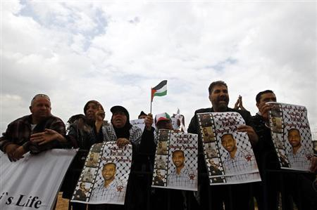 Palestinian protesters hold placards during a demonstration in support of hunger-striking Palestinian prisoner Samer al-Issawi, outside Kaplan hospital in Rehovot near Tel Aviv April 22, 2013. REUTERS/Ammar Awad