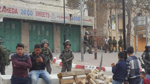 Soldiers escort heavily-armed colonial settlers during an hours-long incursion into H1, near Shuhada Street.