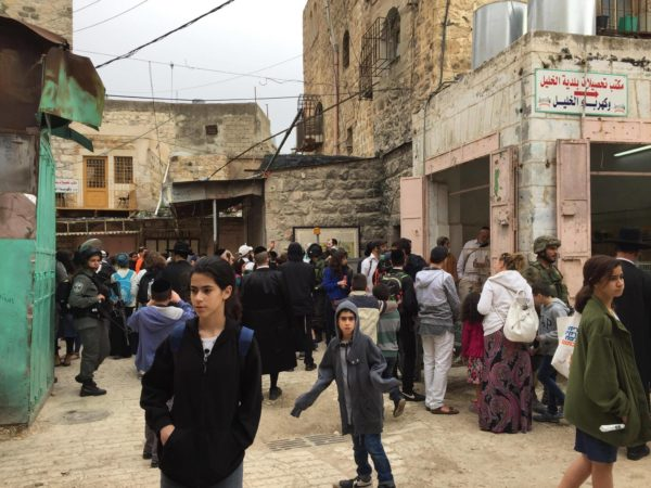 A group of colonial settlers make their way through the Palestinian souk, escorted by heavily armed Israeli forces.