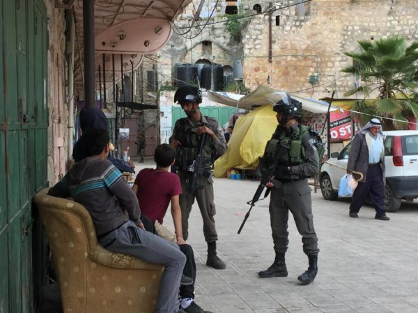 A group of Palestinian boys are questioned by Israeli Border Police in the souk, al-Khalil's Old Town.
