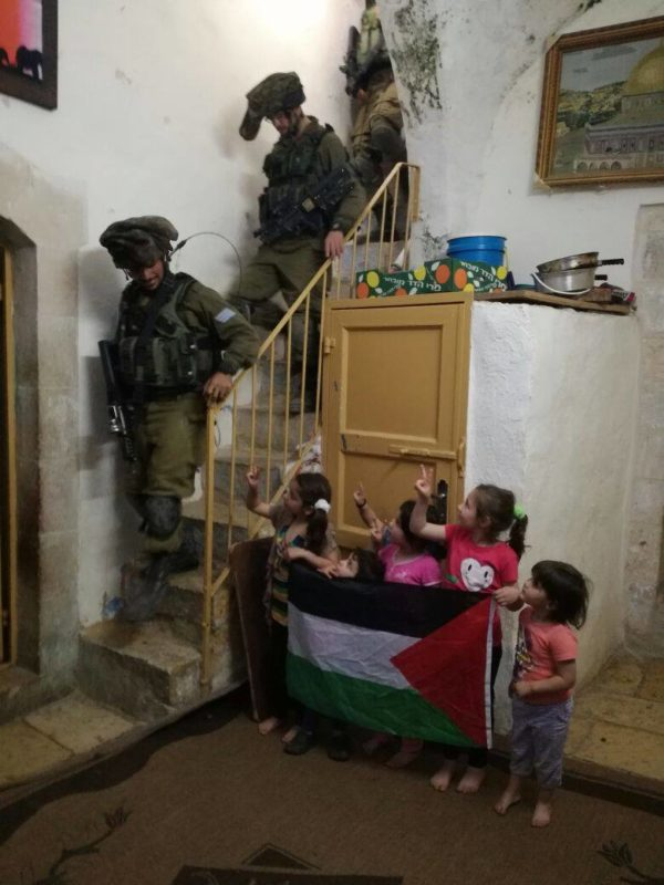 Israeli soldiers walk down the stairs of the family home, where some of the children wait, after occupying the roof.